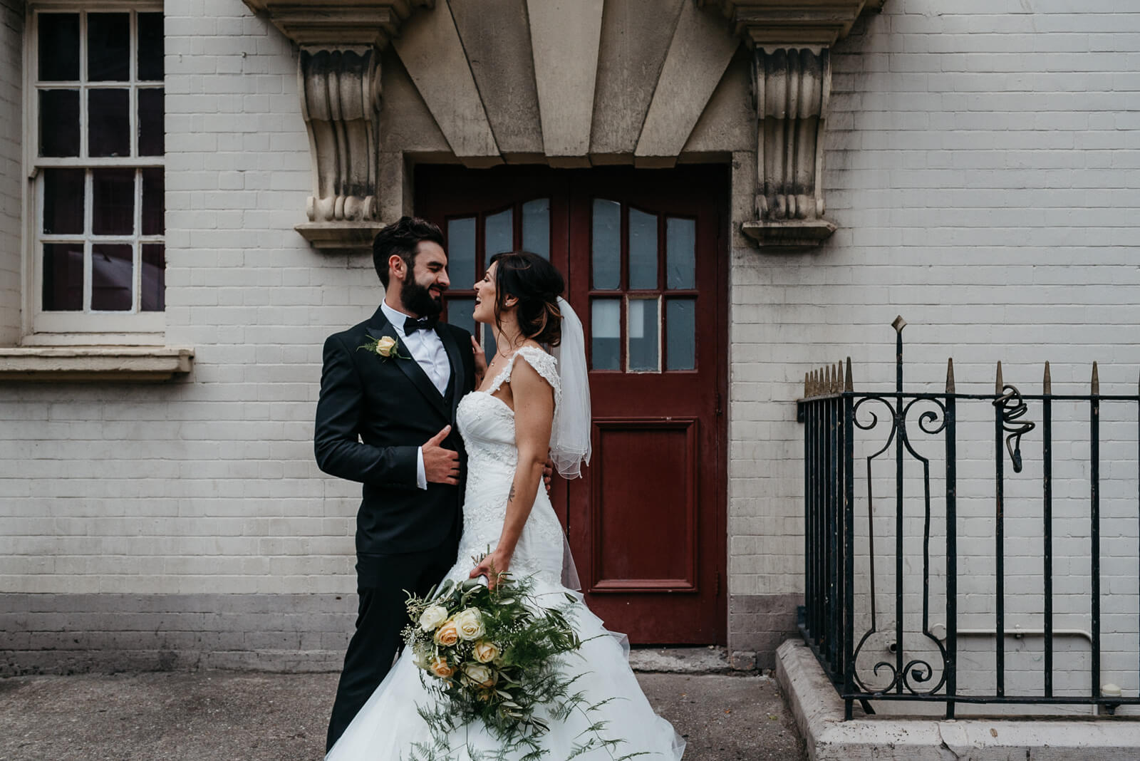 bride and groom stop in front of pretty doorway for portraits