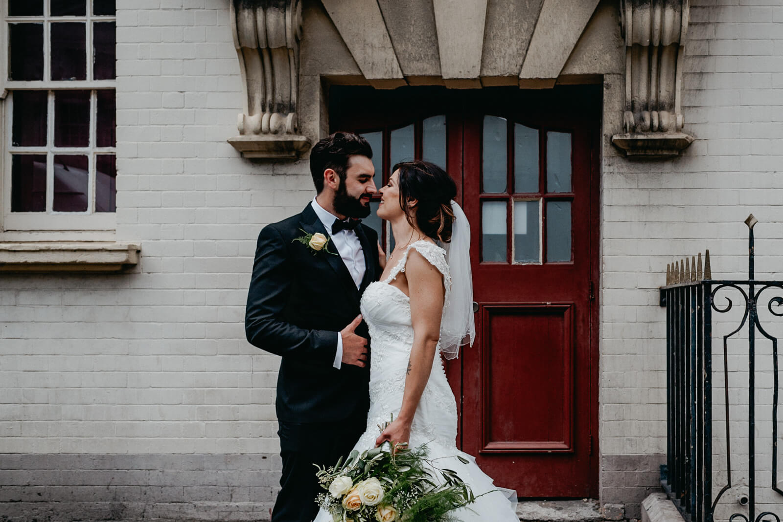 bride and groom wearing black tie in front of red door in cardiff