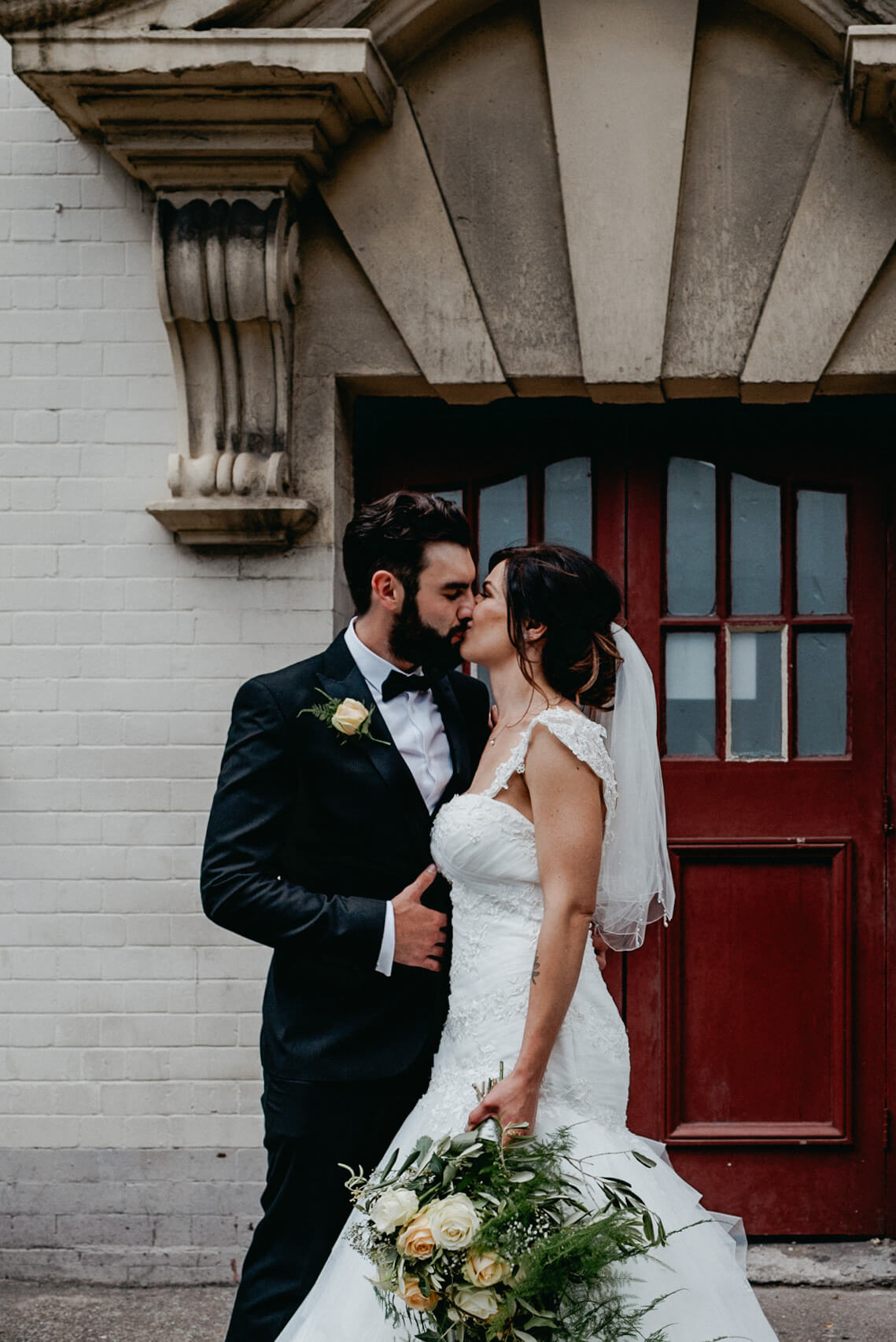 bride and groom kiss in front of red door in sity