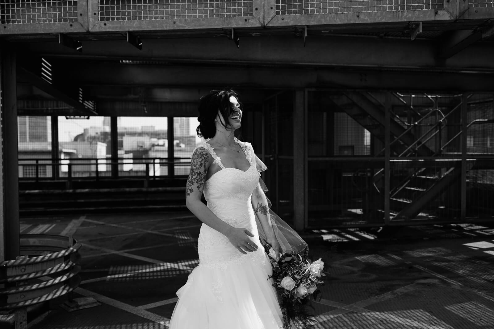 black and white portrait of bride laughing on carpark