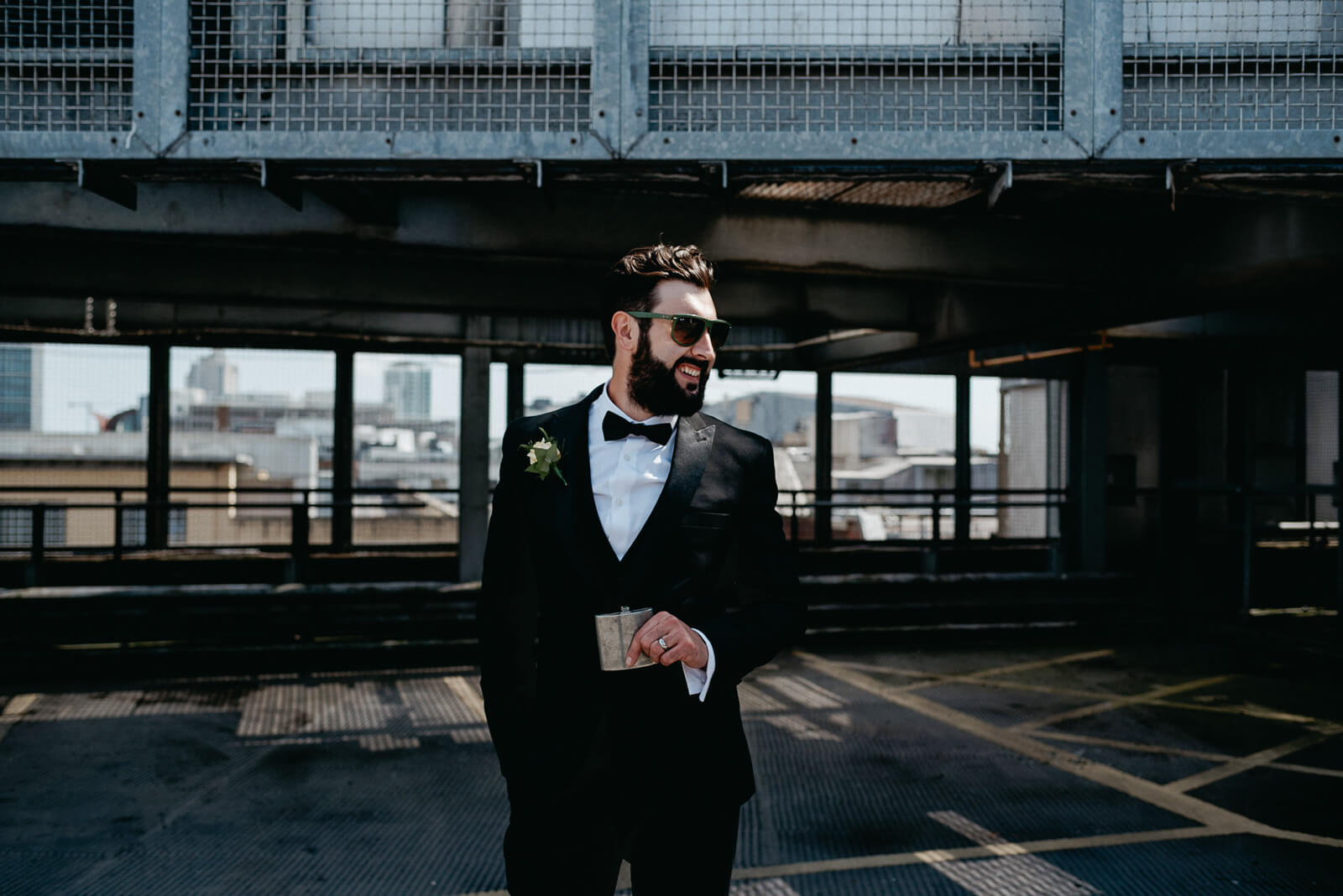 dapper city groom on rooftop for portraits following city hall wedding