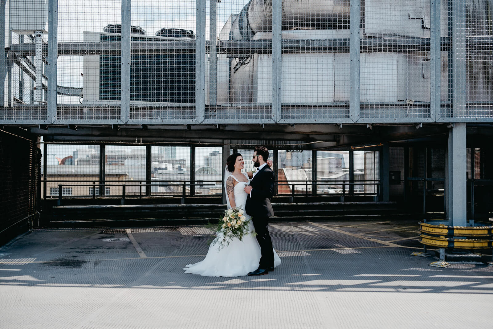 Bride and groom in industrial setting for alternative, modern wedding portraits in the city