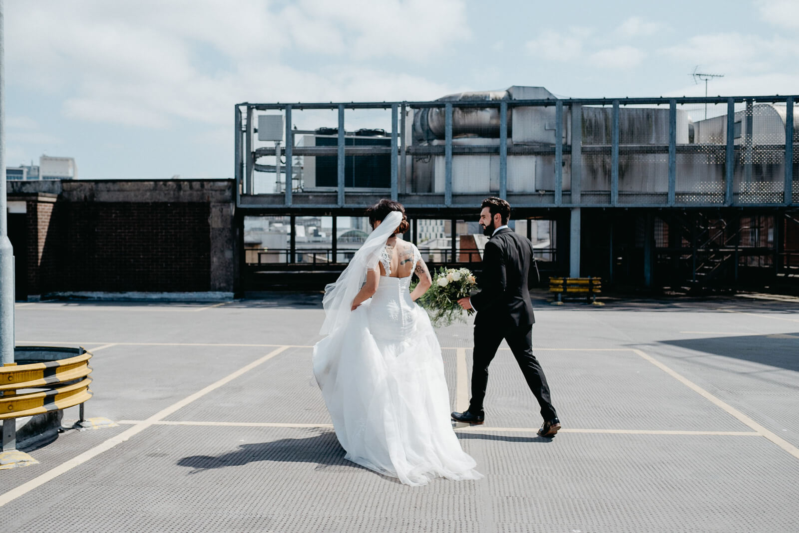 modern bride and groom on city rooftop taking in urban vibes of city