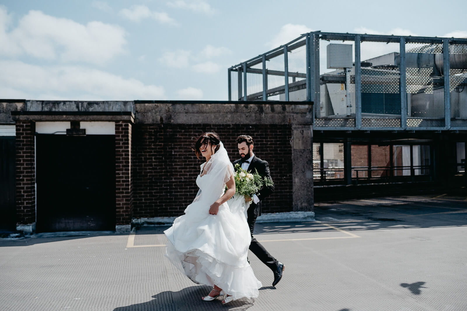 bride and groom walking away following their couple roof on city rooftop