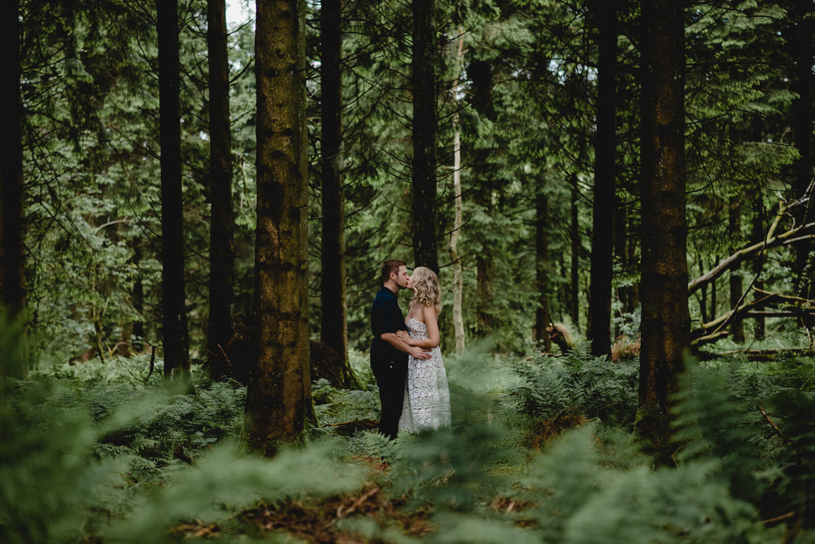 bride and groom sharing a kiss in woodland