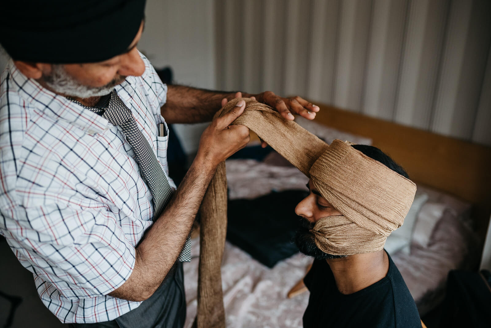 Groom's uncle helps tie gold silk turban or pagari for Indian fusion wedding in London