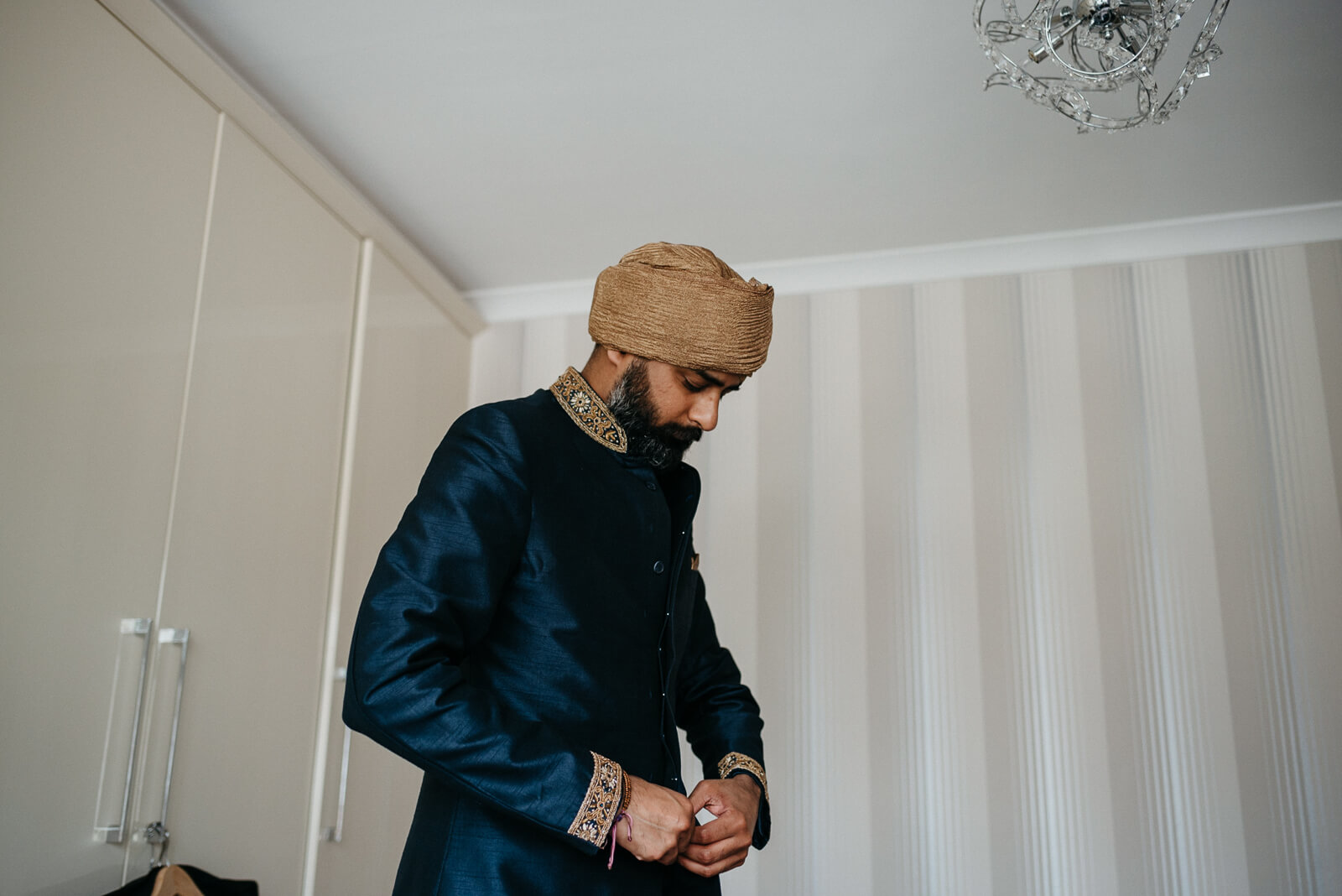 London Indian groom getting dressed in his navy silk wedding suit
