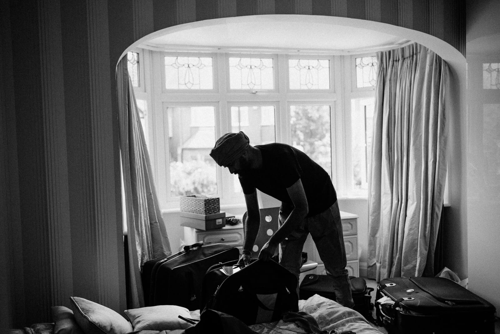 moody black and white photograph of groom getting ready in London