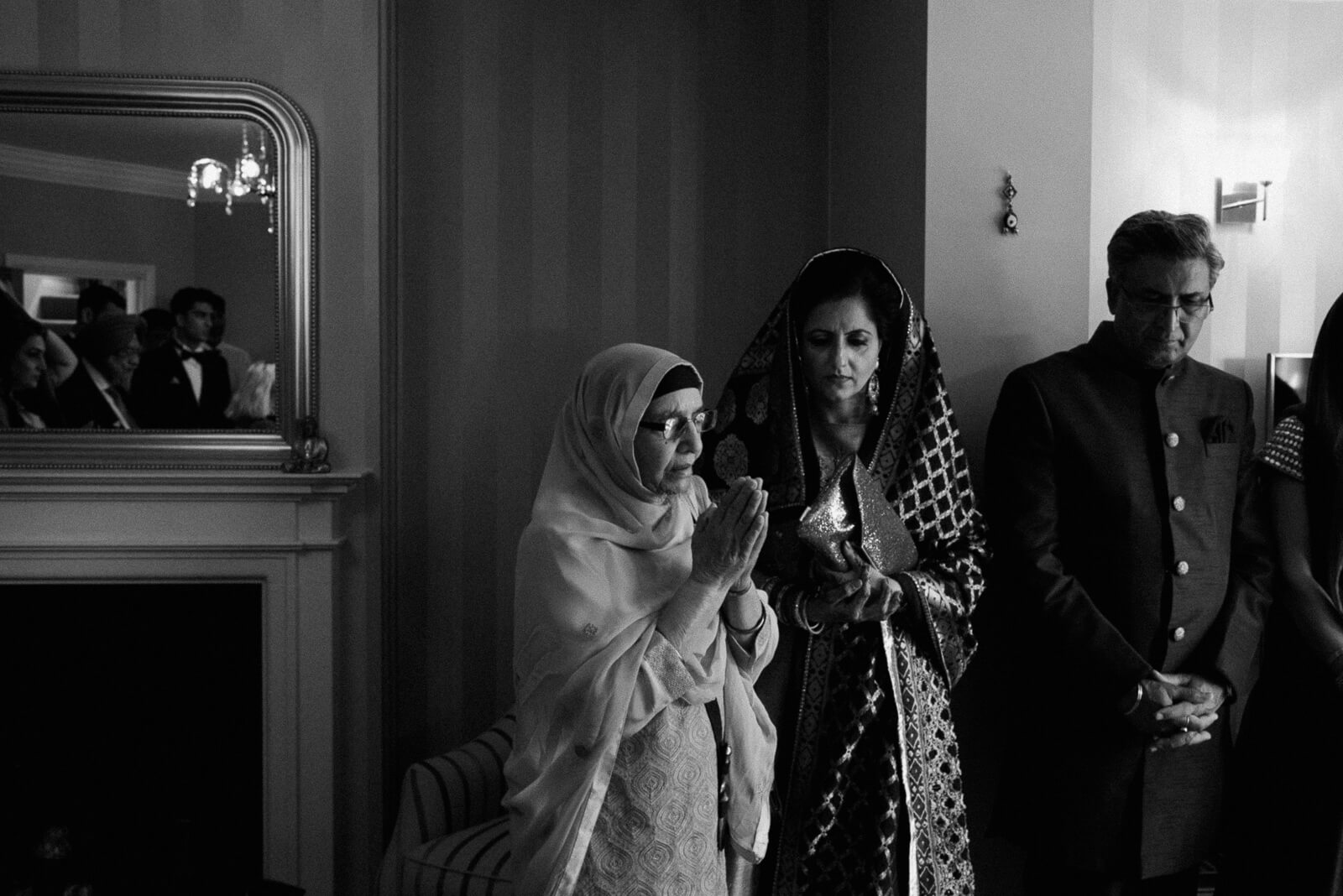 Hindu grooms family pray before he leaves for his humanist wedding at Marylebone One, London