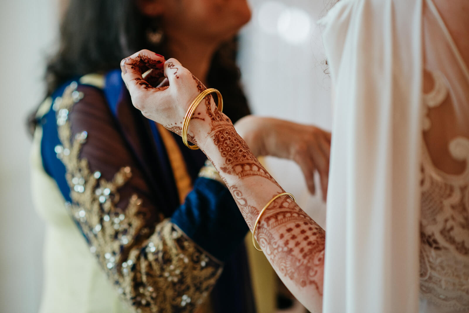 Brides mendhi and gold bangles at her fusion wedding in Londons Marylebone One