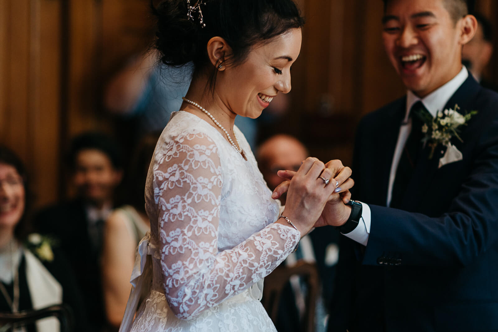 London Bride laughing as she puts wedding ring on her husbands finger