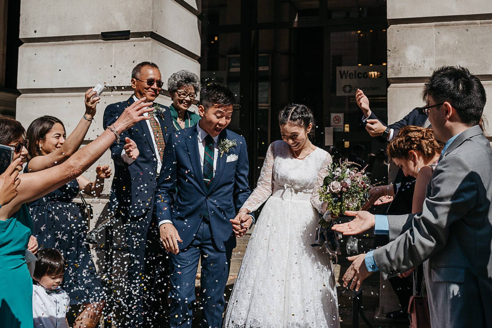 bride and groom with confetti on steps outside Camden Town Hall in London