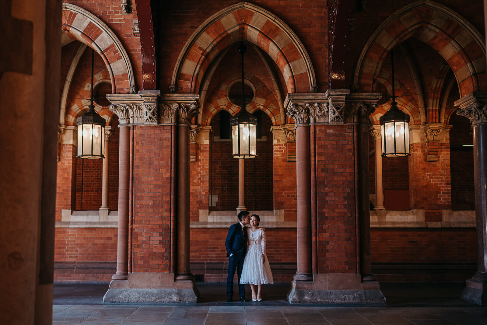 Bride and groom standing in arch way at St Pancras Station in London