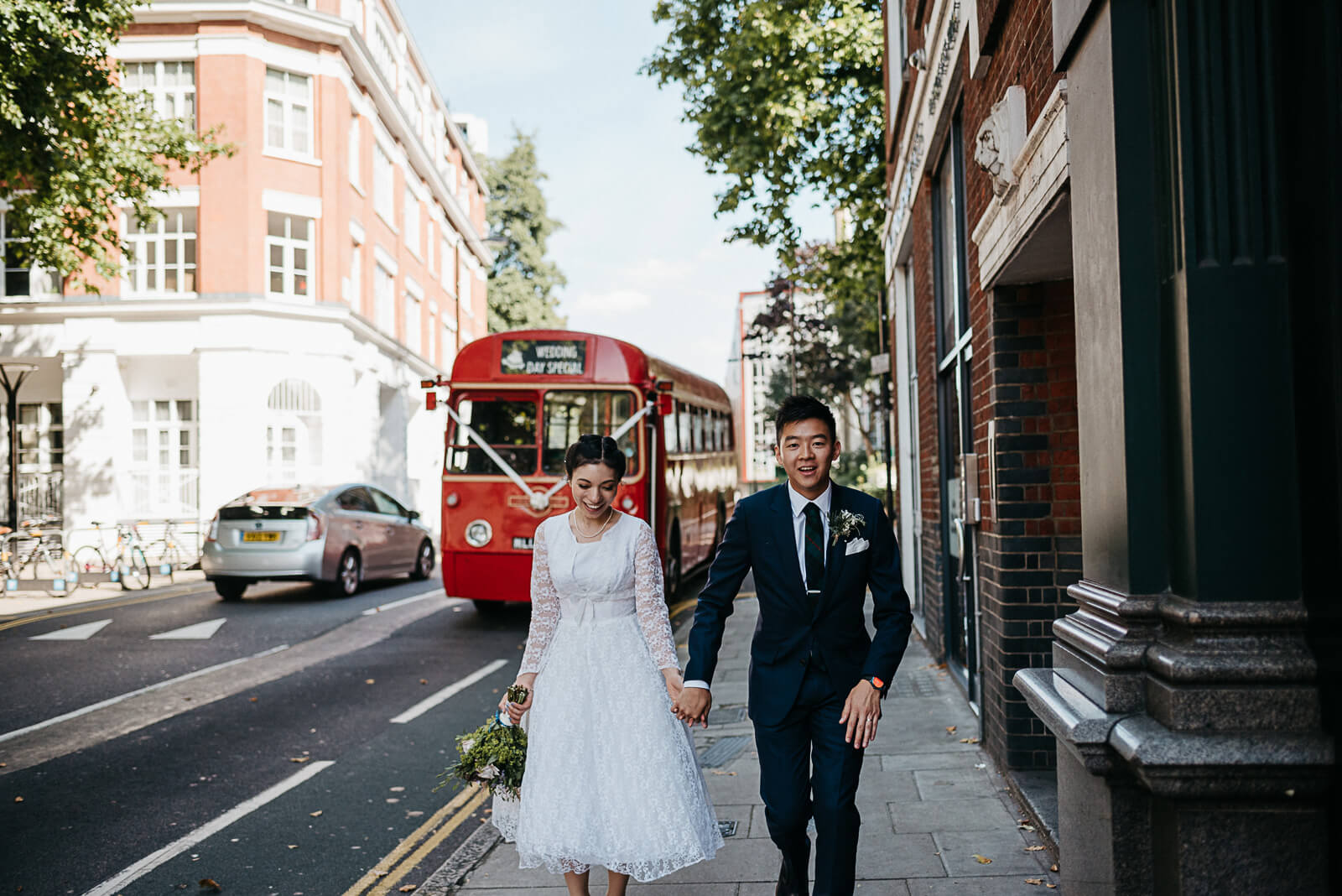 Bride and groom walking away from vintage red London Bus towarsds the Peasant Pub in Clerkenwell
