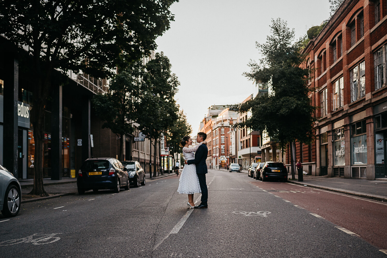 couple take a moment from their peasant pub reception stop for portrait in road in Clerkenwell