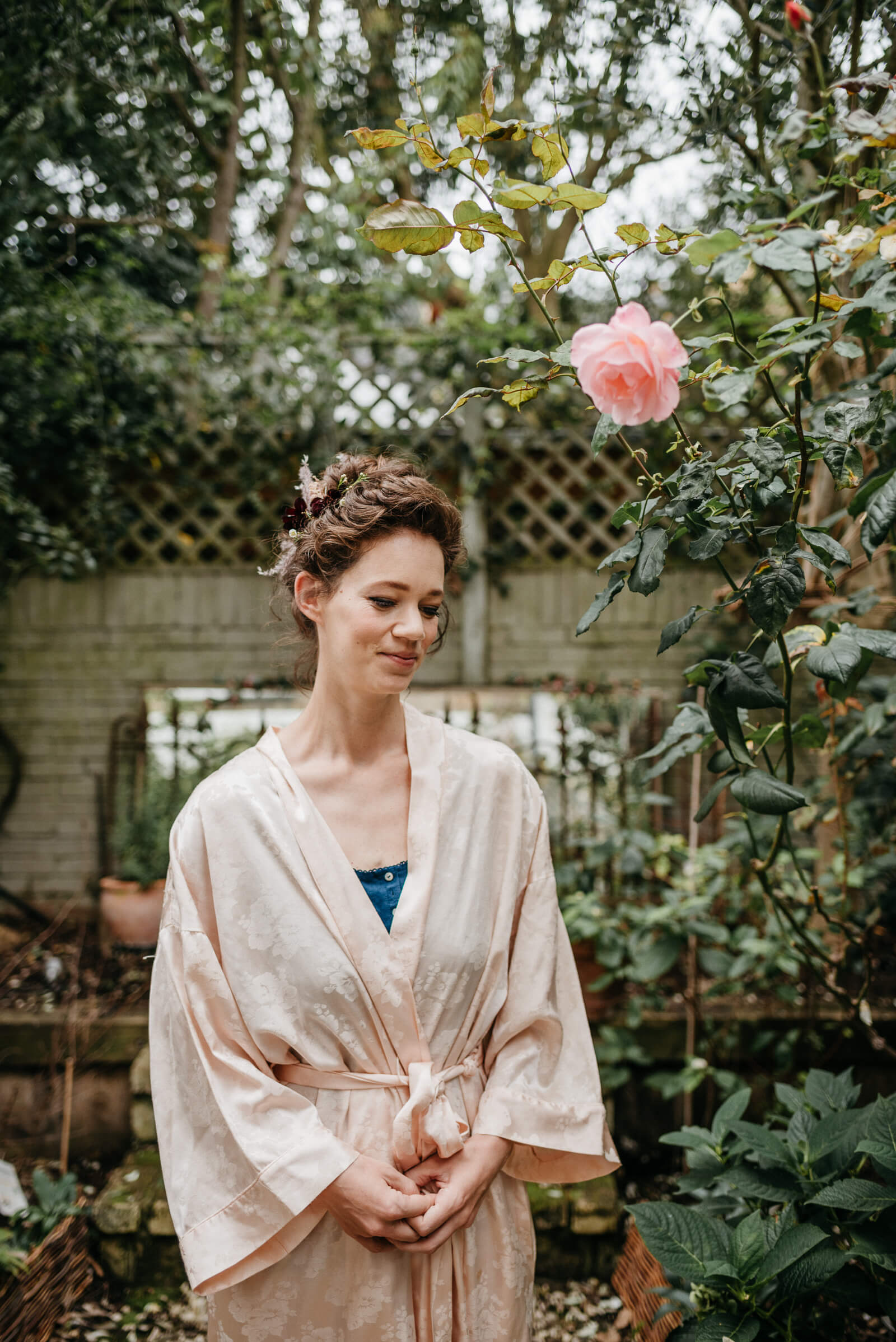 portrait of London bride in garden with pale pink rose wearing pale pink kimono
