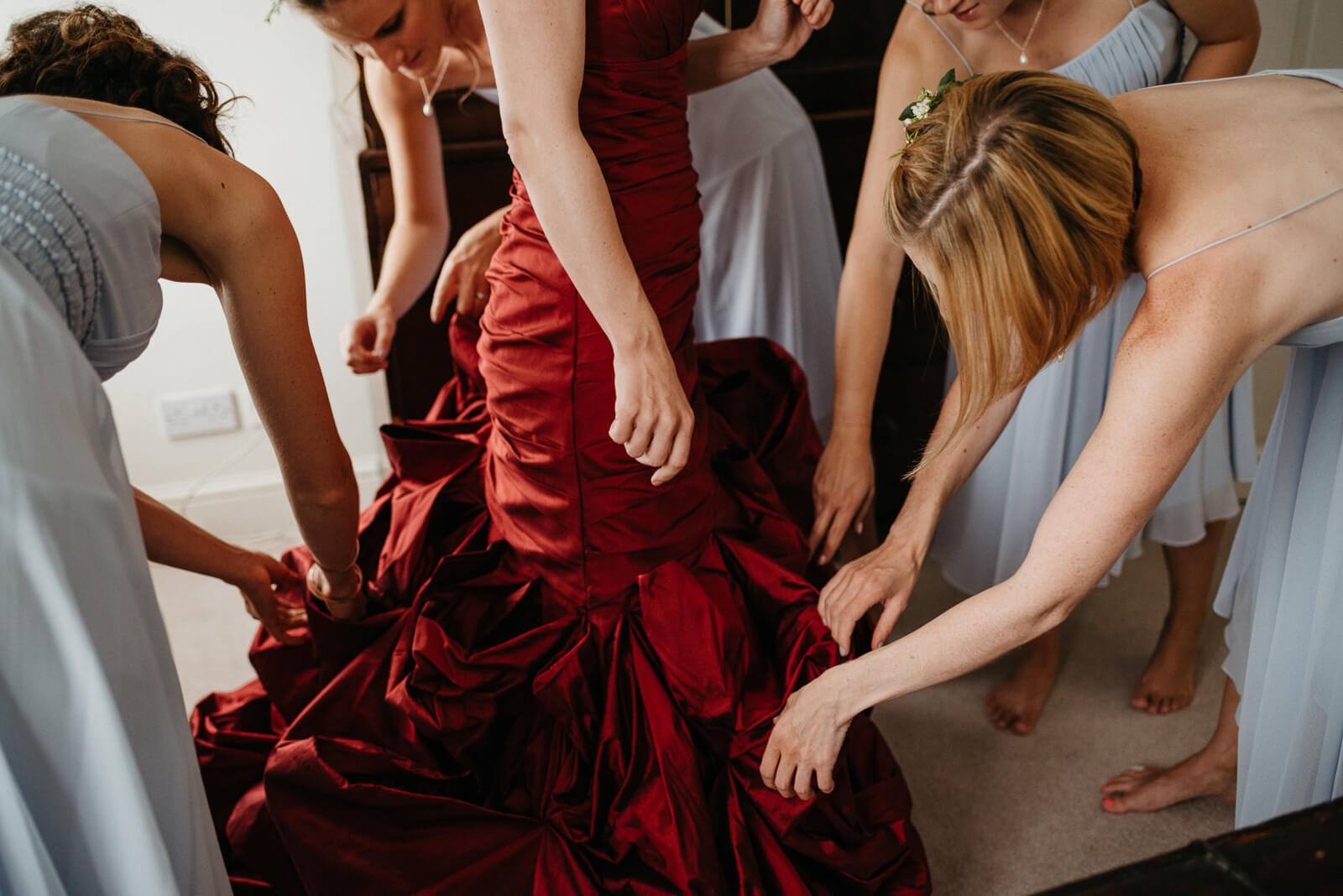 bridesmaids fuss with red taffeta wedding dress during morning getting ready