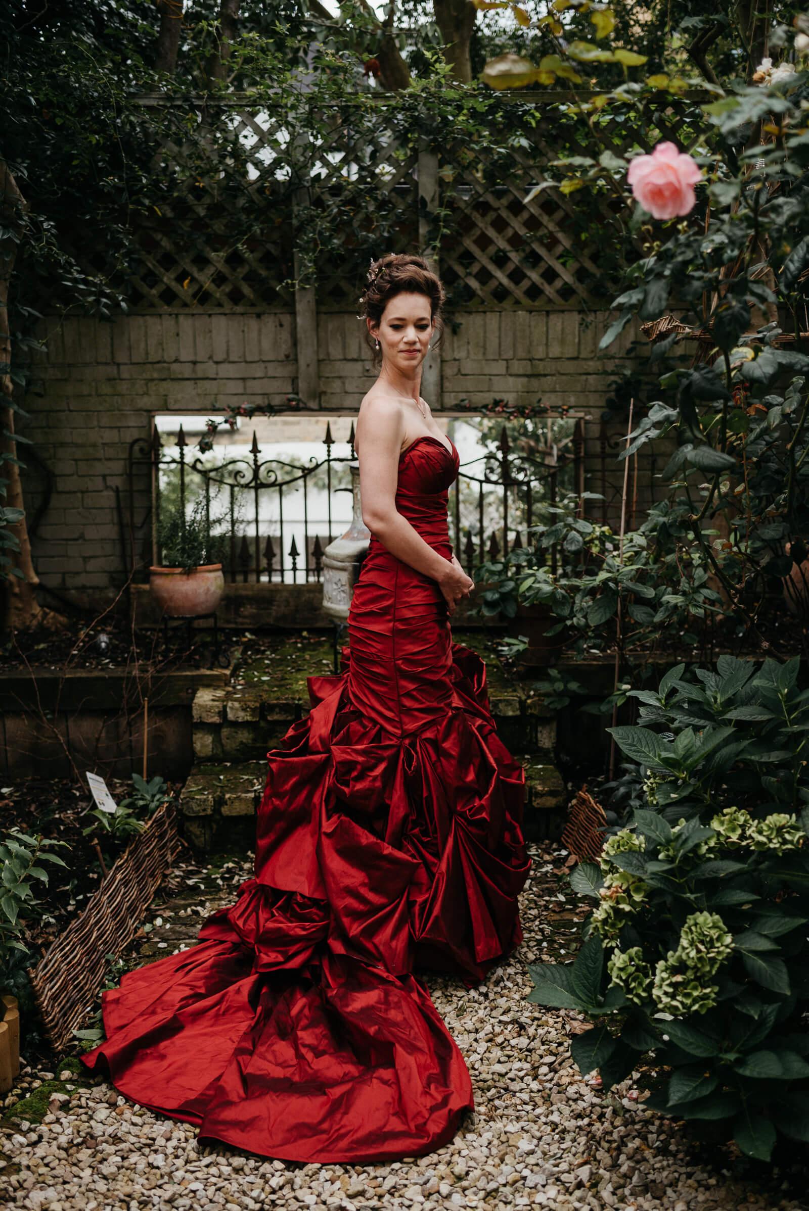 portrait of bride wearing her alternative red taffeta wedding dress in Battersea Garden