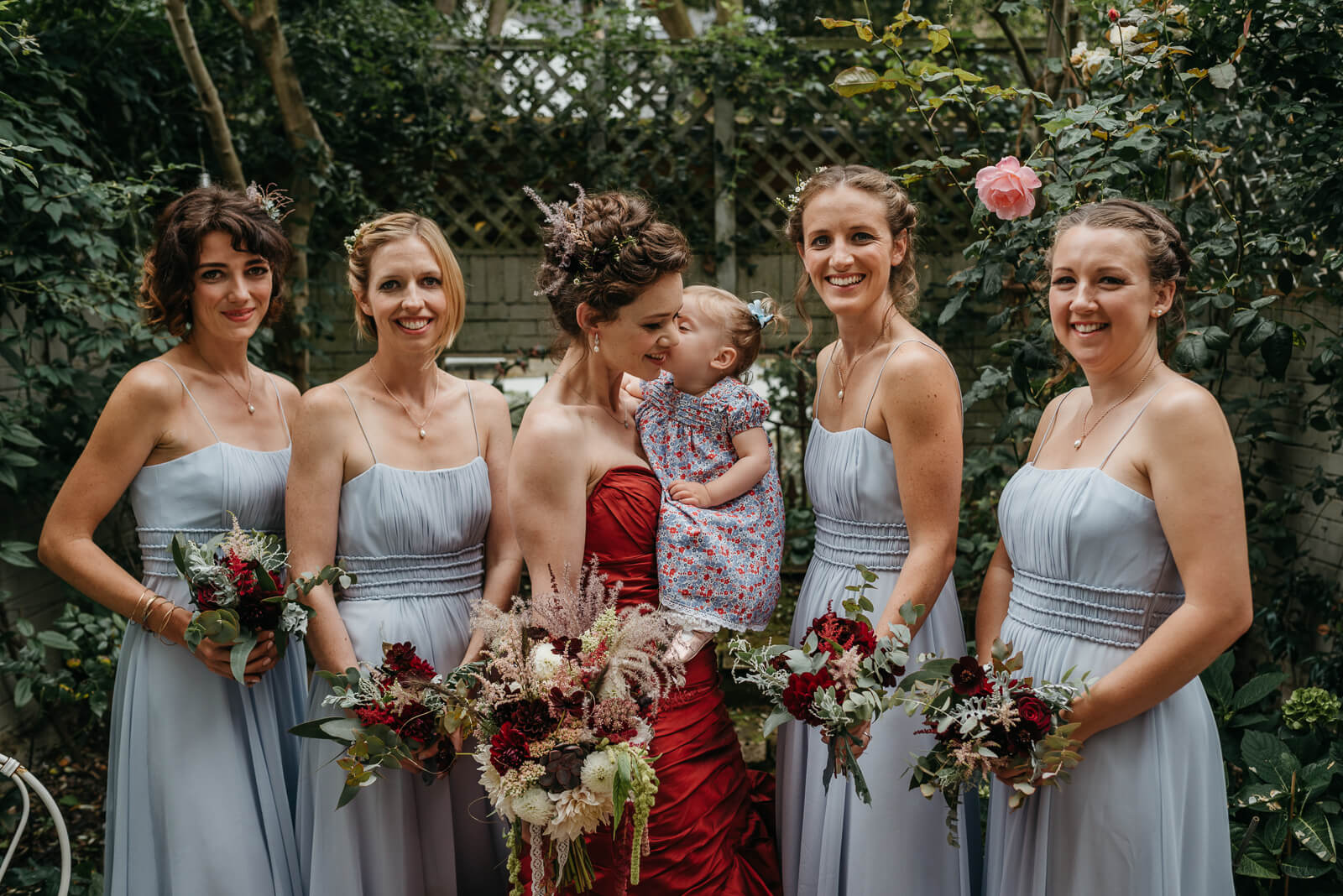bride and bridesmaids laugh in garden holding their bouquets