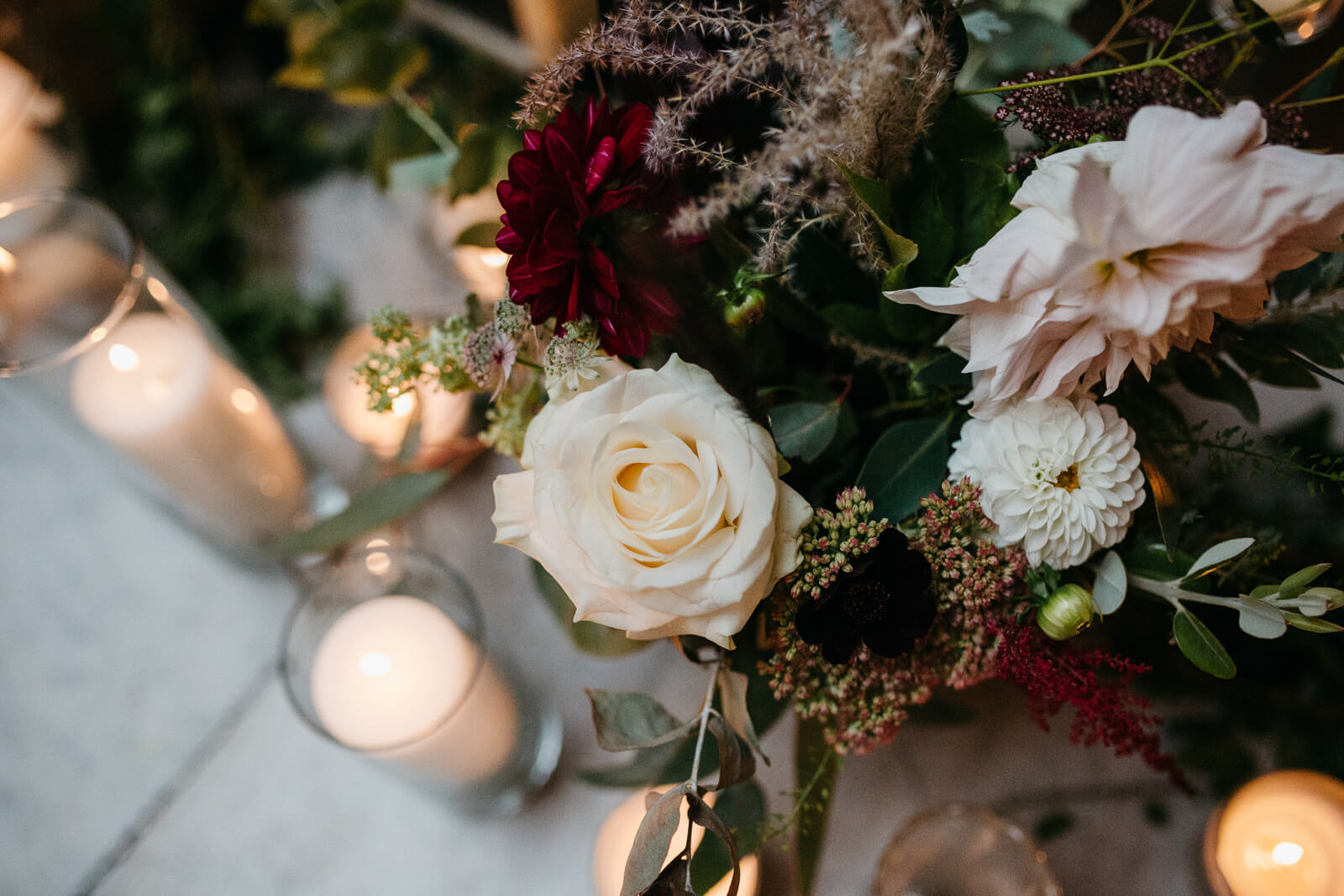 white roses and wine dahlias and hurricane vases with church candles on stairs at London wedding venue