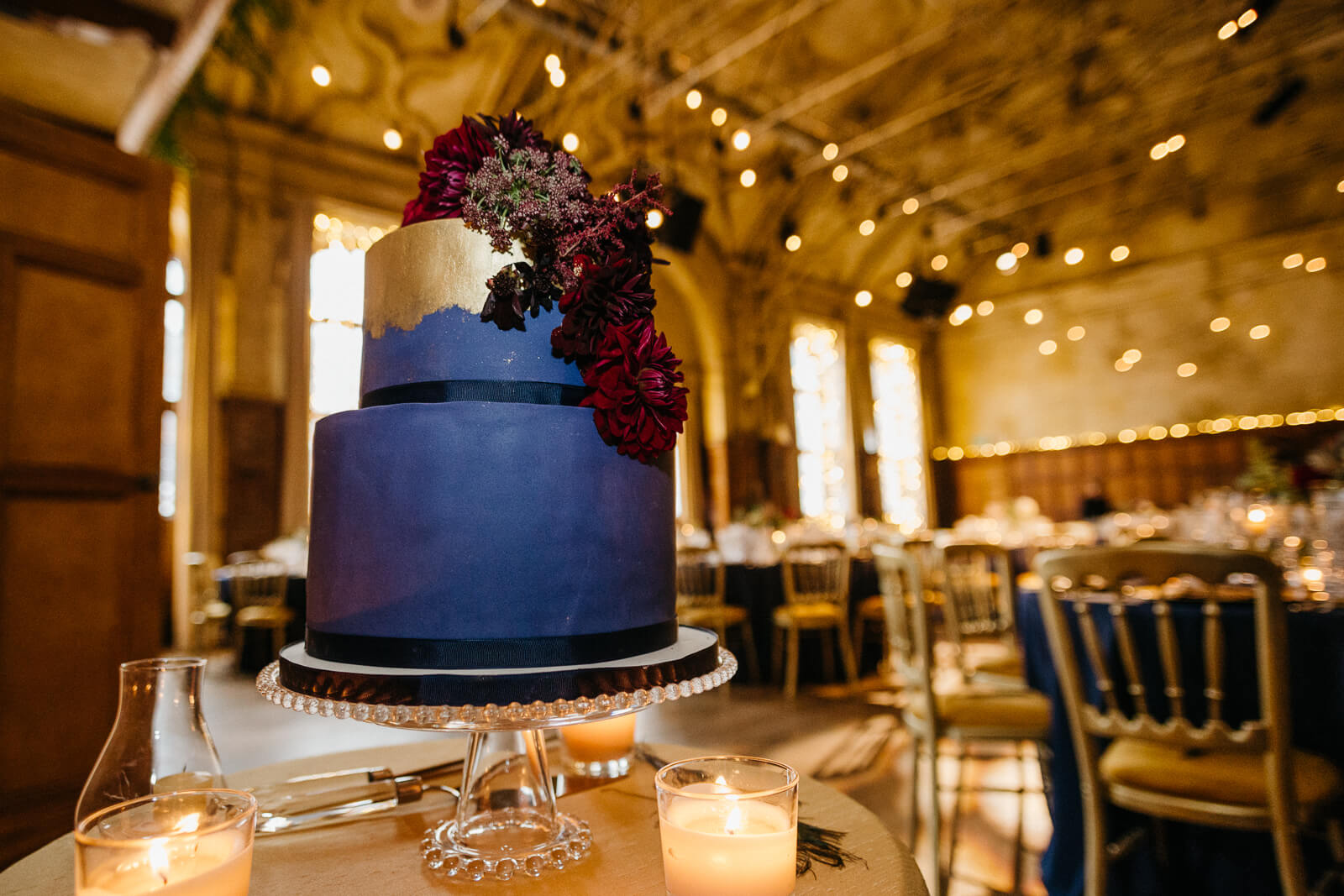 luxe gold and purple cake with warm glow of fairy lights in the background