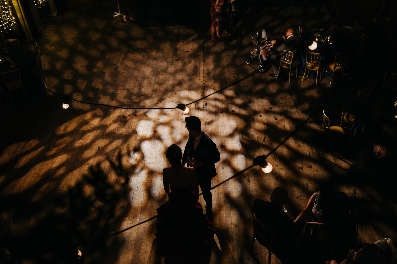 creative documentary photograph of bride and groom as they dance under festoon lighting