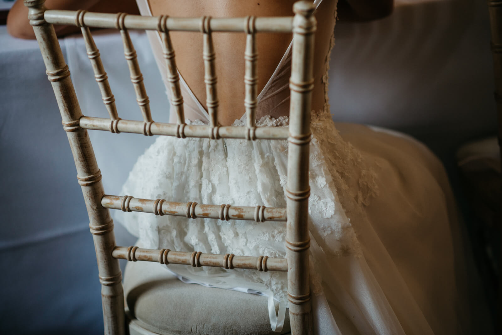 Fine art portrait on the bride wearing Cymbeline sitting on a bamboo chair