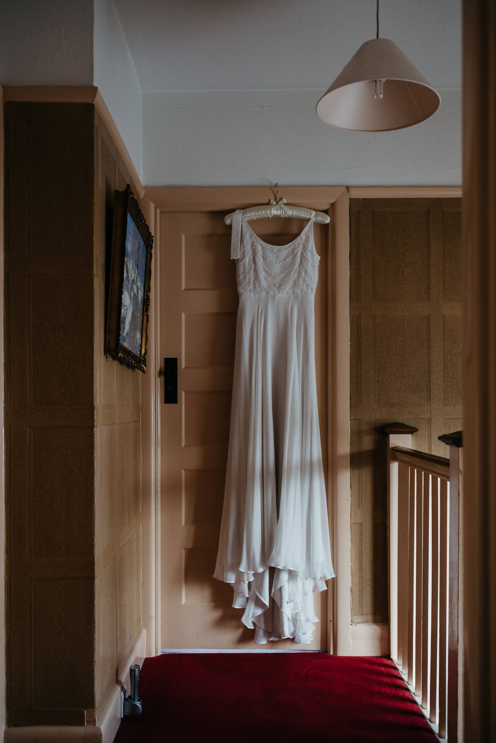 Brides Sally Eagle dress hanging in moody daylight at her parents London home