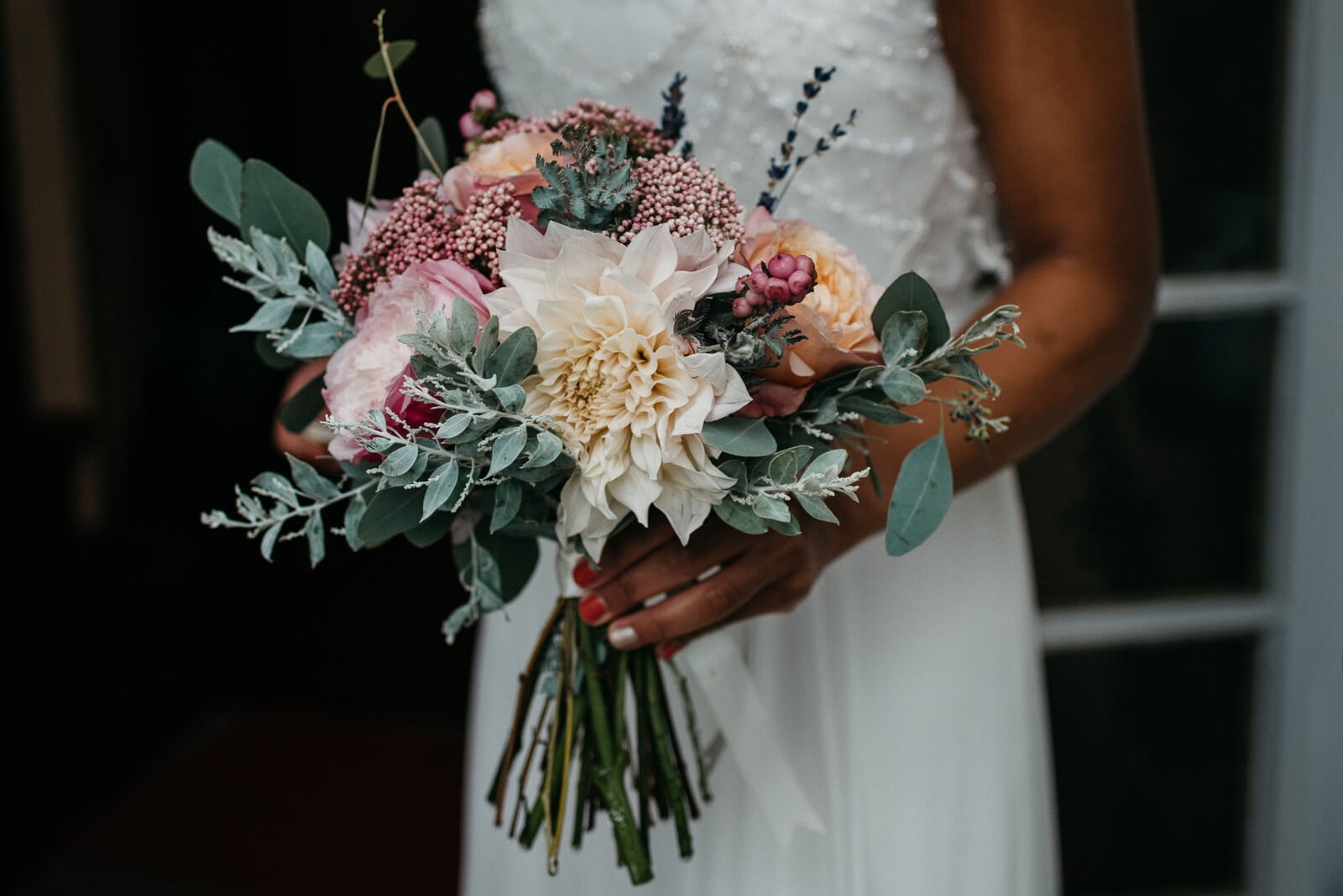 bride holding her stunning bouquet of cream dahlias, eucalyptus, apricot david austin roses and foliage