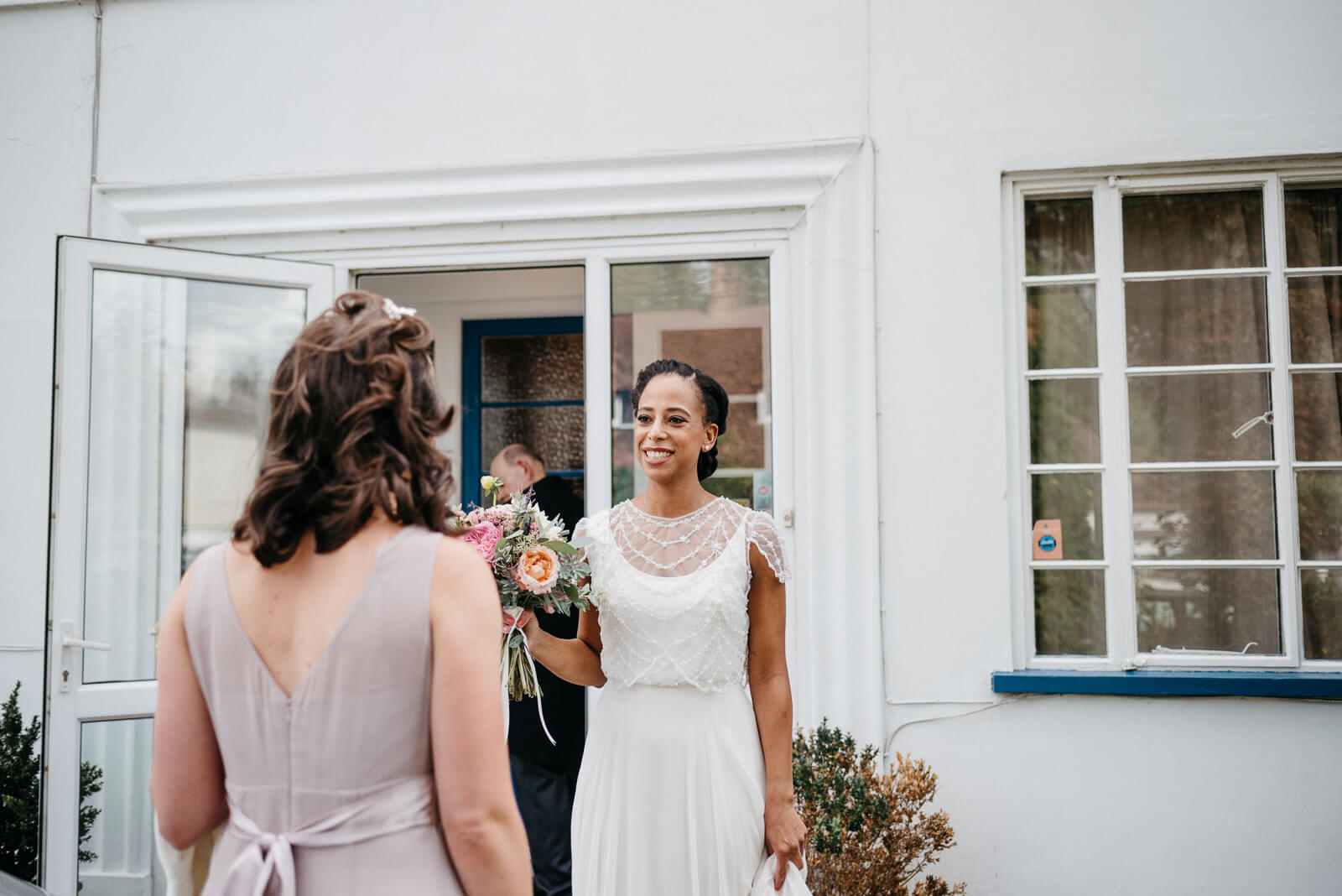bride smiles at her bridesmaid as she leaves her parents London home for her wedding at Hampton Court House