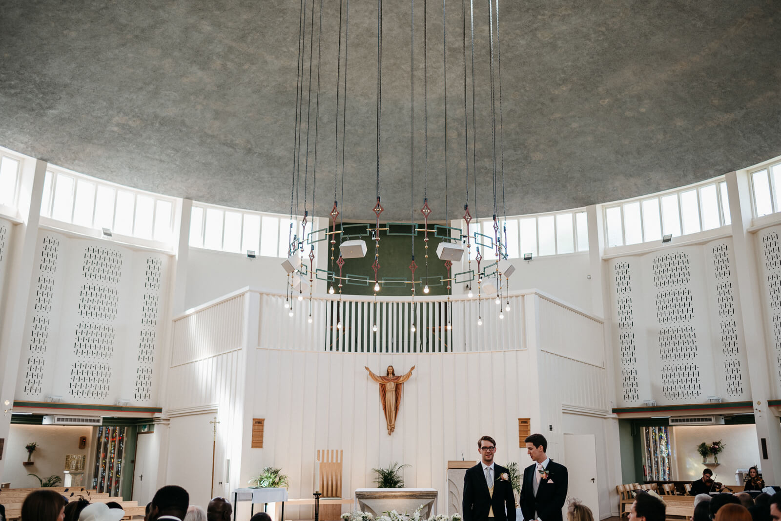 Groom & best man wait inside stunning roman catholic church in London