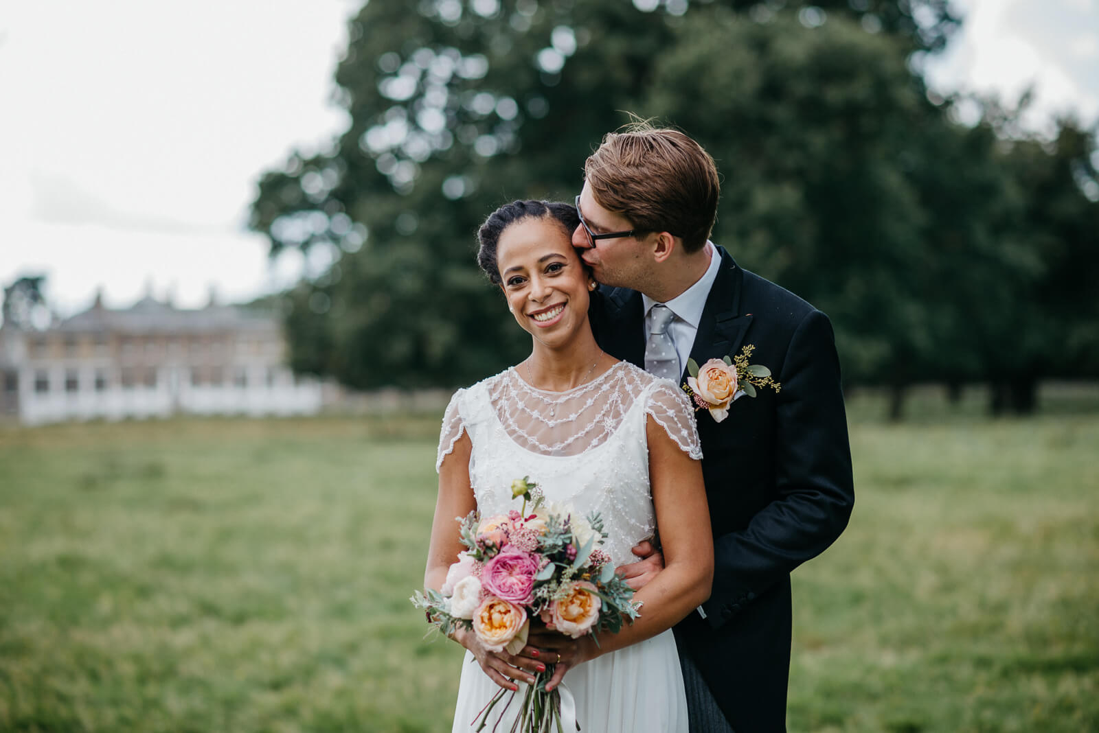 Groom tenderly kisses brides cheek in Bushy Park