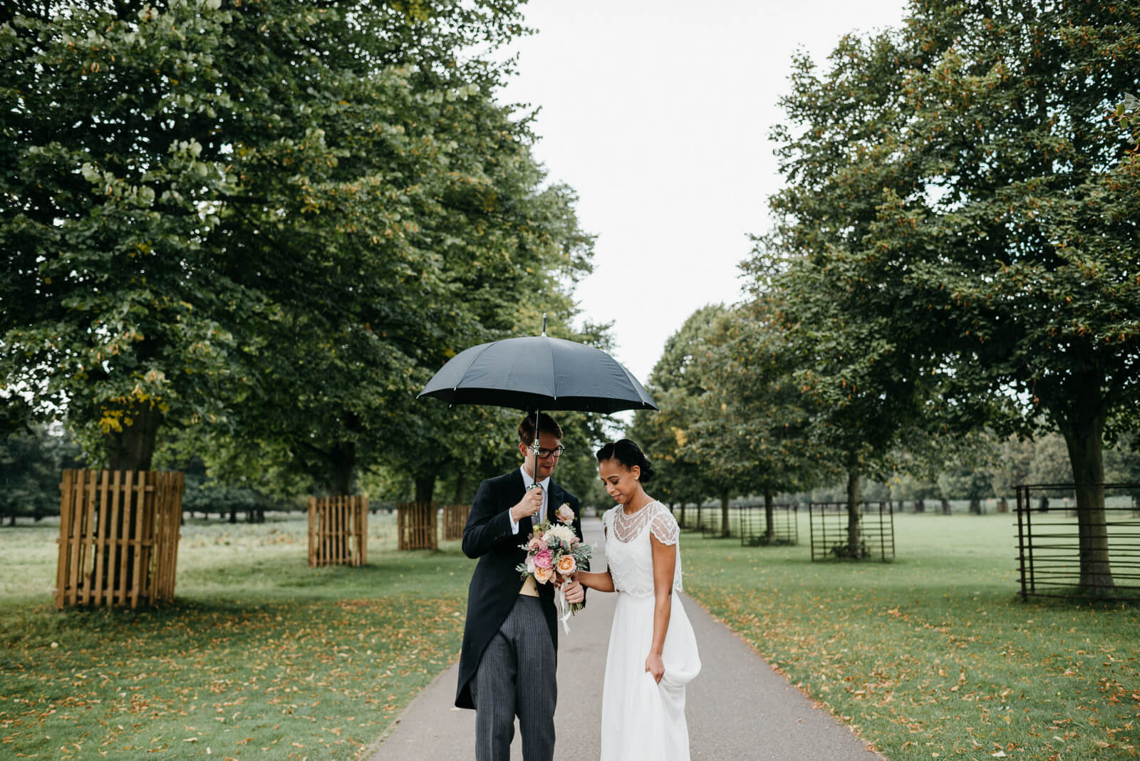 bride and groom shelter from passing rain shower under umbrella in Bushy Park