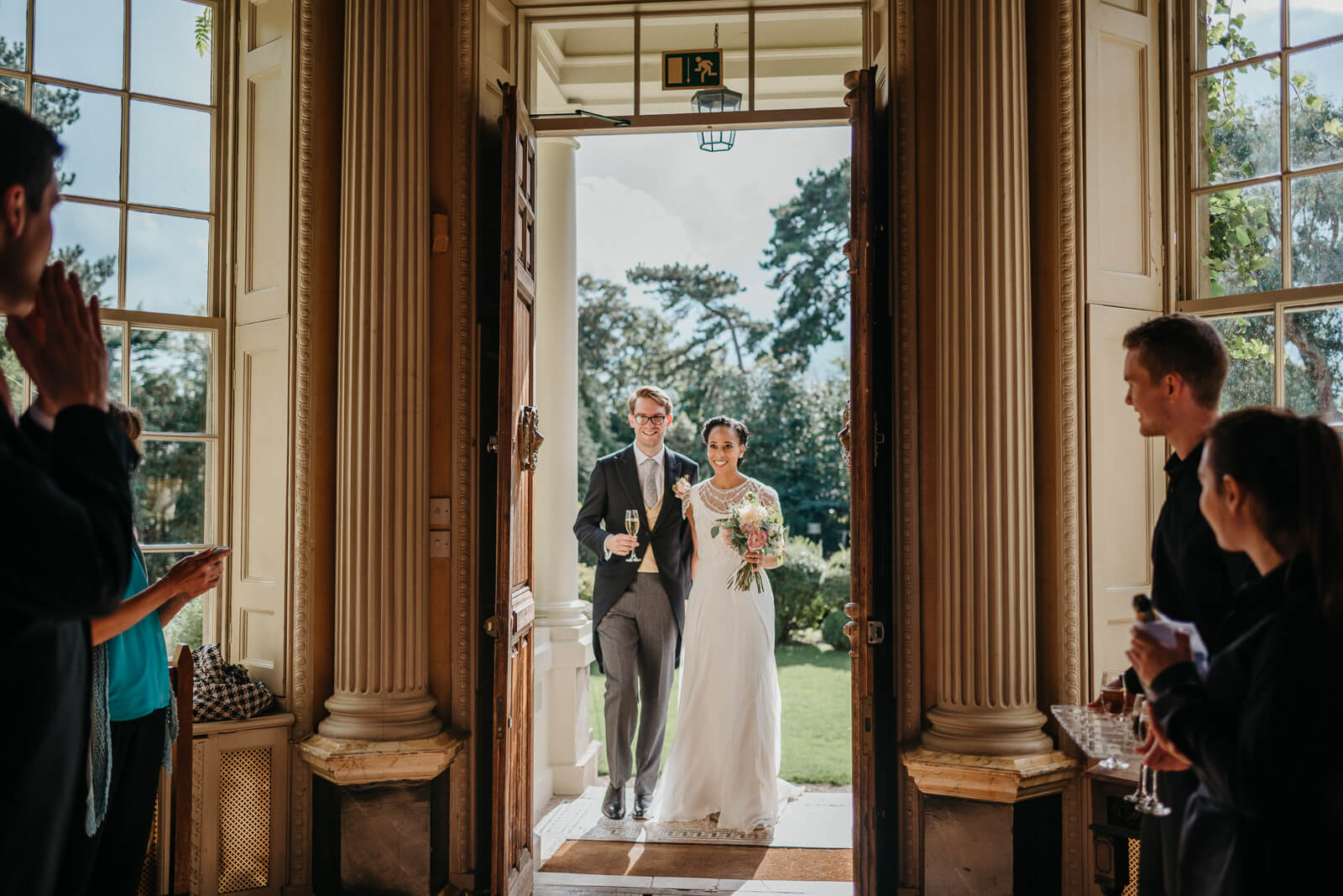 Bride and groom entering Hampton Court House for their wedding celebration