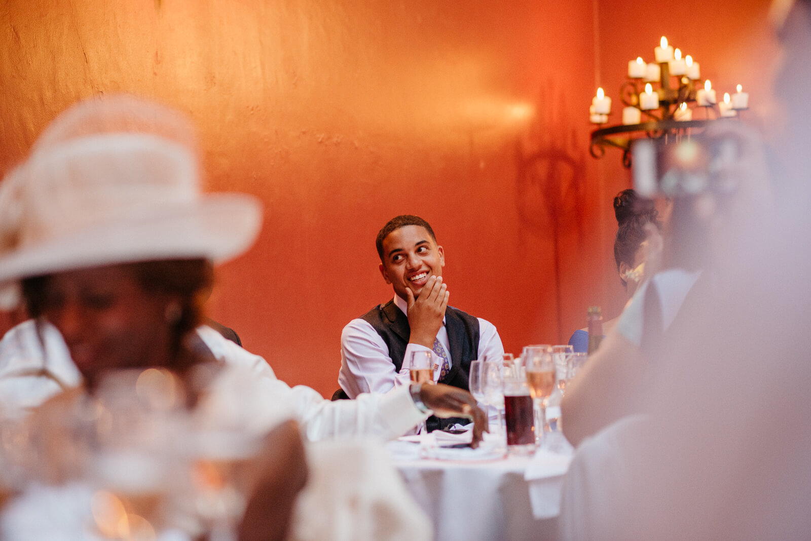brides brother looks on smiling coyly while his sister delivers her speech during dinner