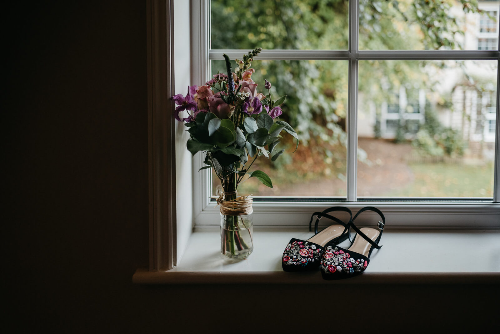 brides wildflower bouquet and flat embroidered shoes on window ledge of Hampshire New Forest hotel