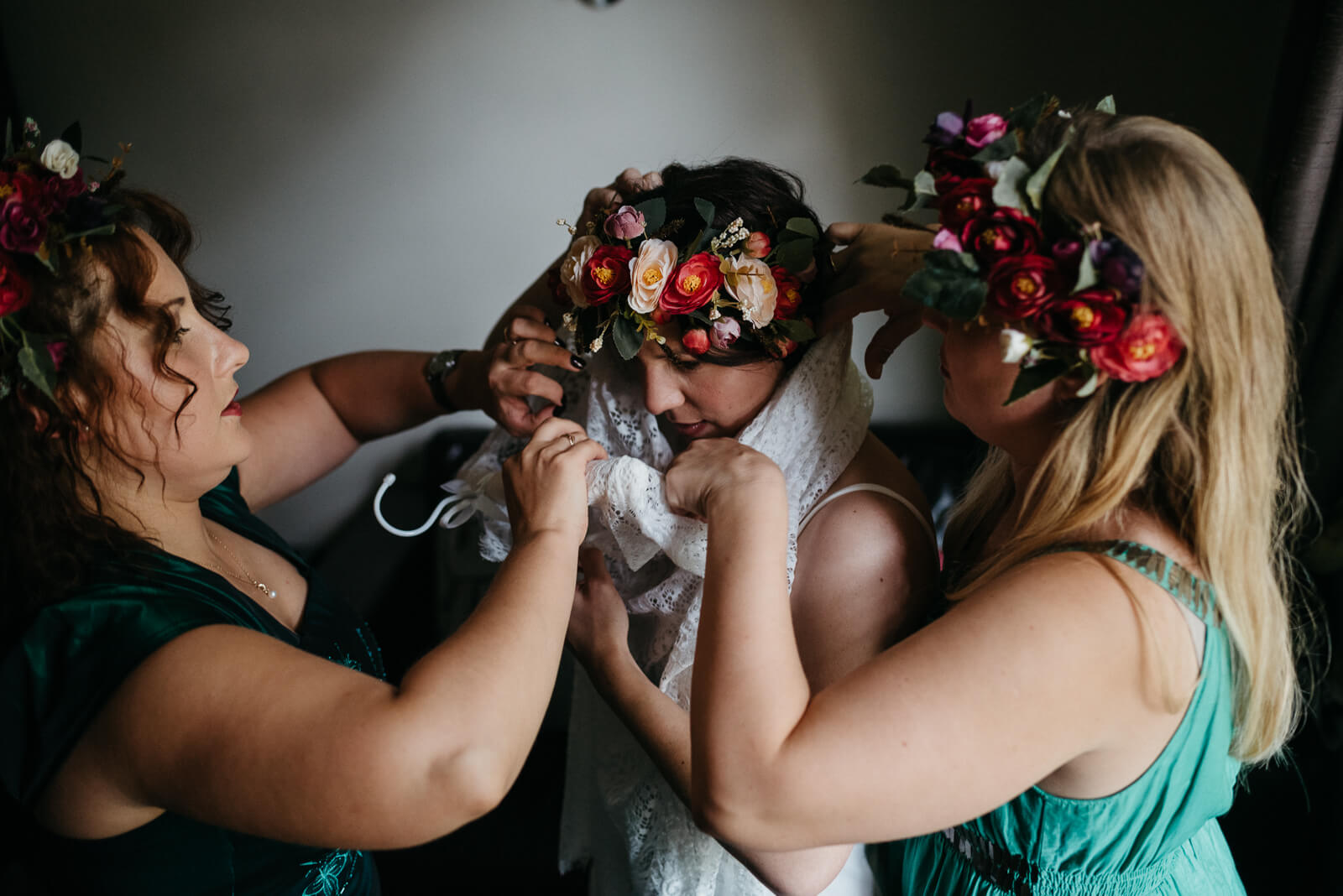 boho bride putting on her lace wedding dress while wearing a red and whit floral crown