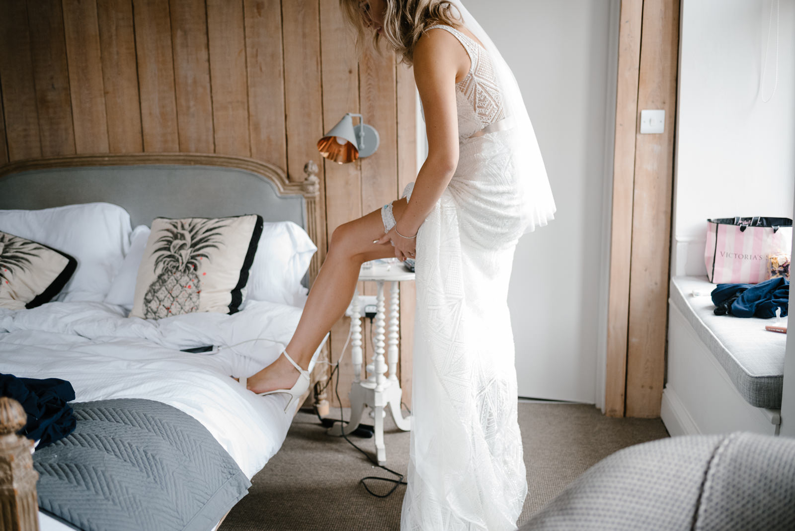 modern bride putting on garter for her modern wedding with industrial vibes