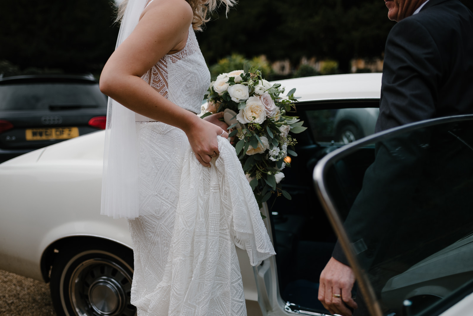 bride getting into her vintage mustang wedding car