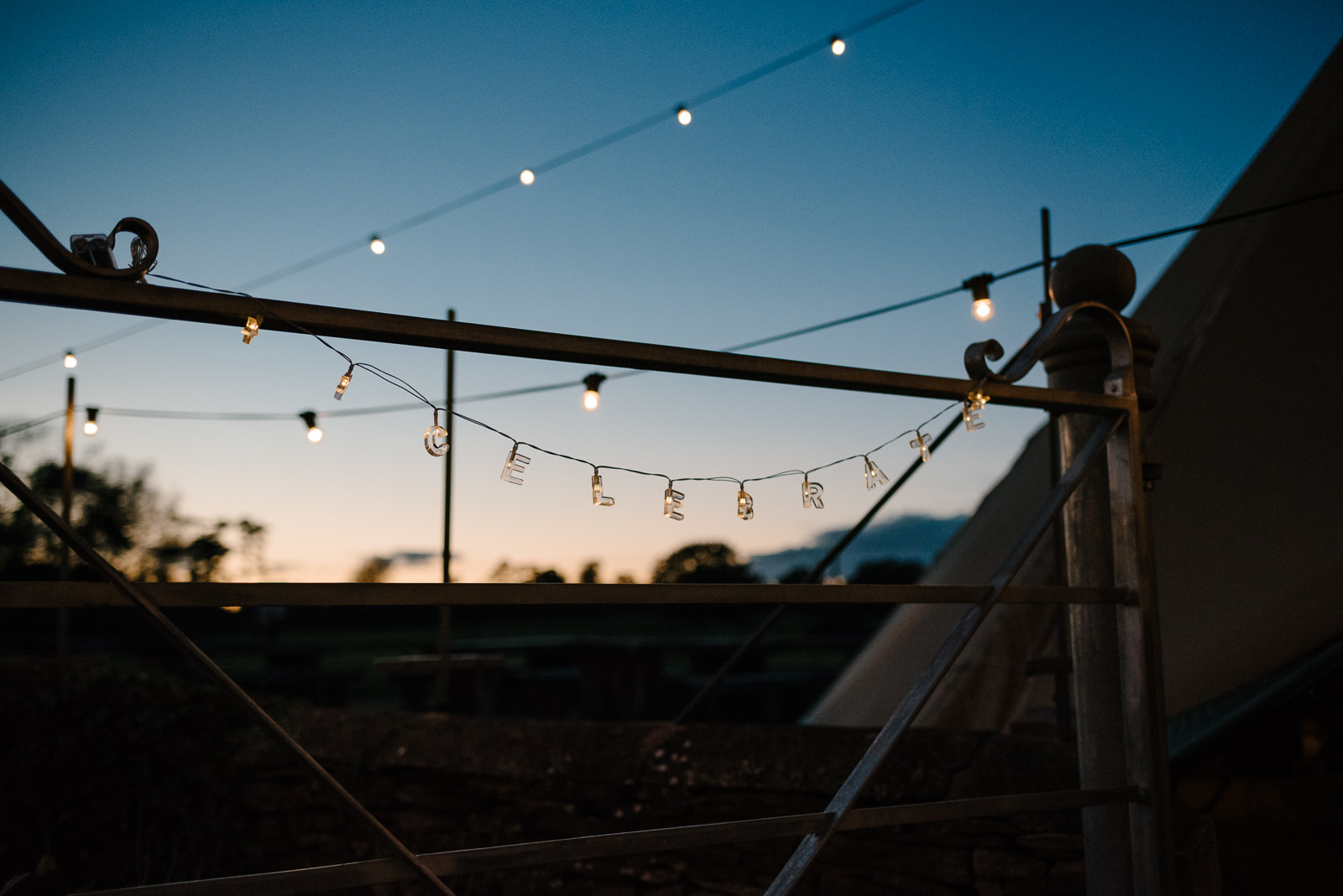 Celebrate' lights hand on field gate at modern Wiltshire wedding