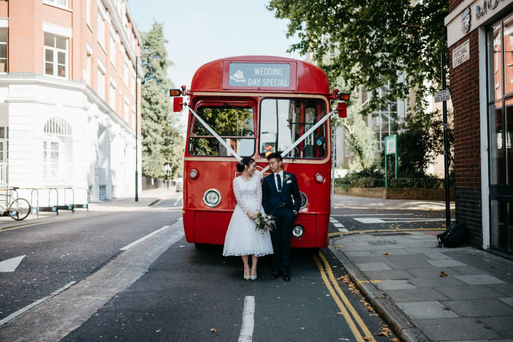 stylish and modern Bride & Groom stand in front of a vintage red London bus at The Peasant Pub before their wedding celebrations