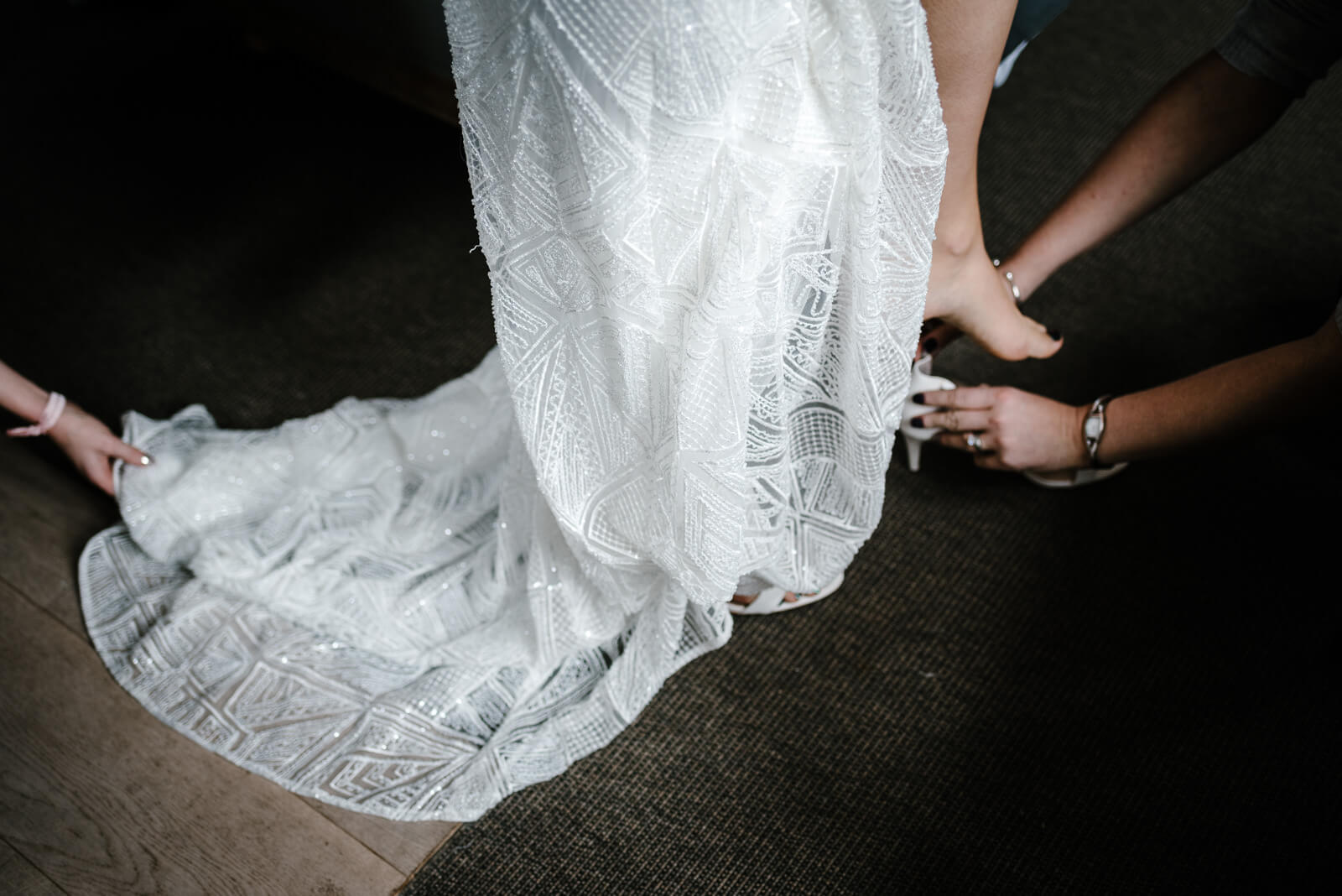beautiful beading detail on brides Willowby by Watters gown while bride puts on her white strappy shoes
