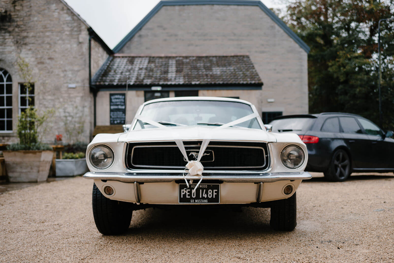 Brides vintage cream Mustang Fastback wedding car outside Timbrell's Yard