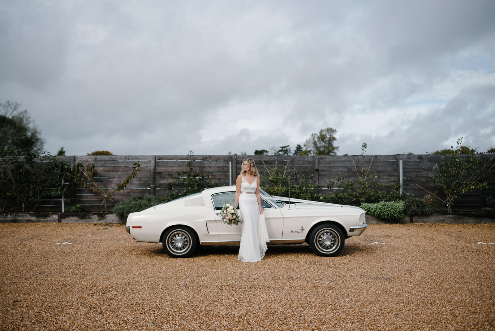 bride standing in front of vintage Mustang wedding car at Glove Factory Studios