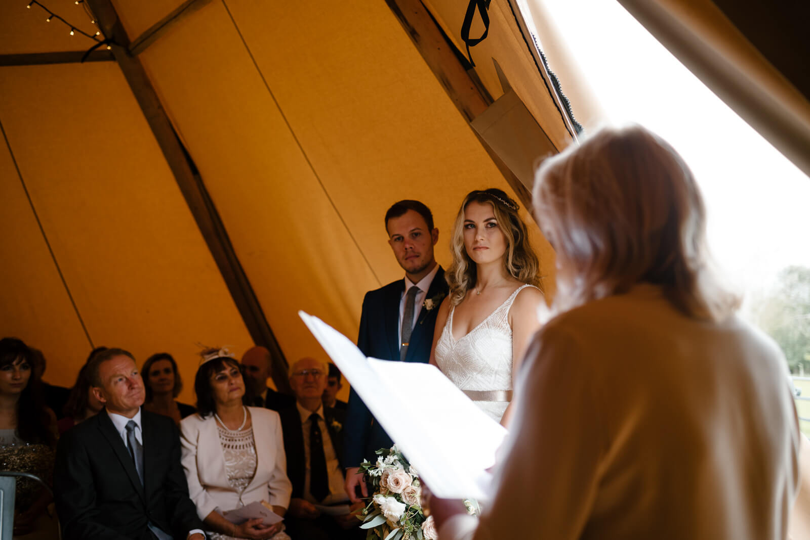 bride and groom look on to registrar during their tipi wedding ceremony at Glove Factory Studios in Holt