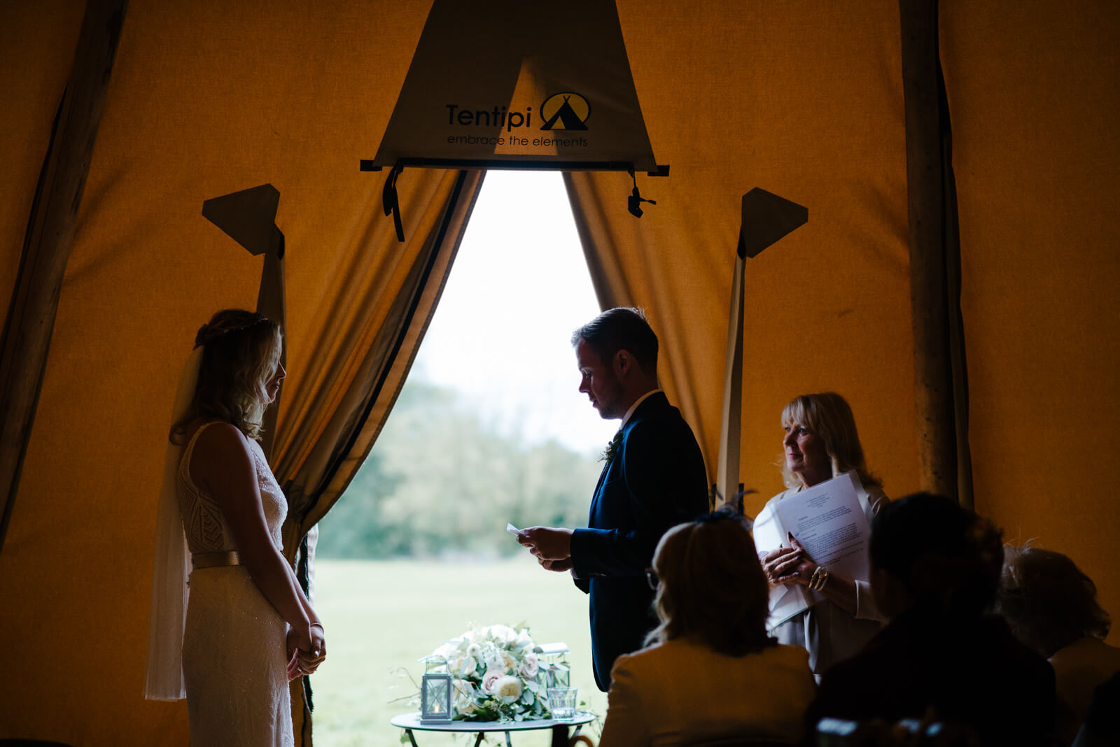 bride and groom exchange vows in dramatic lighting in tipi