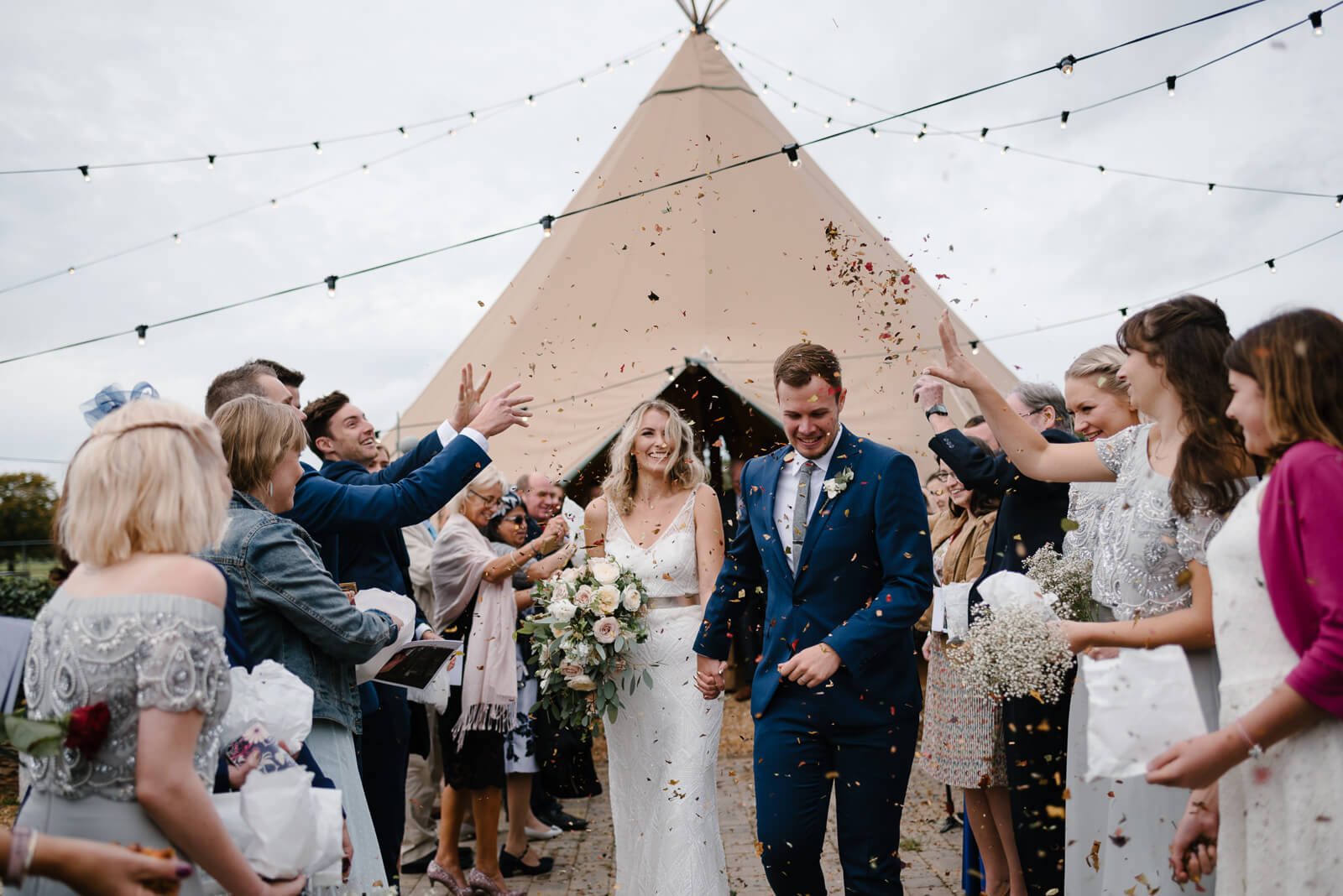 bride and groom walk through confetti at Glove Factory studios wedding in Wiltshire