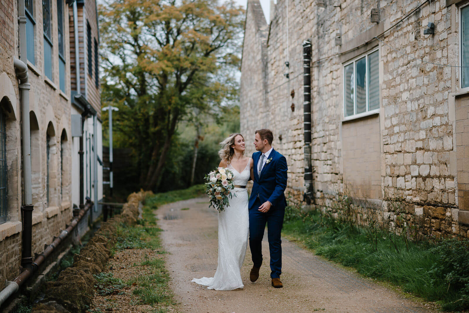 informal portrait of bride and groom as they walk during their Wiltshire wedding at Glove Factory Studios