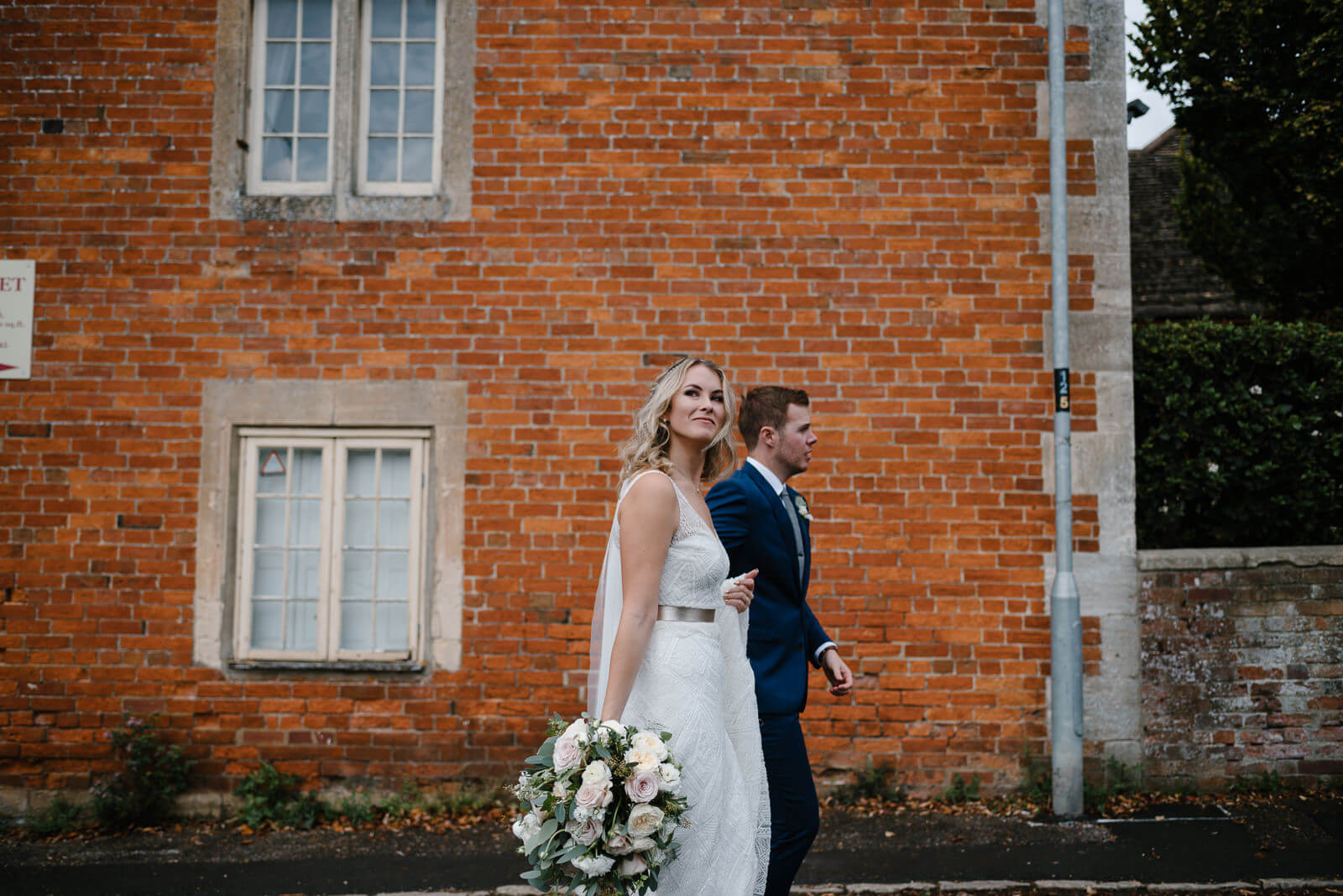 bride and groom strolling past red brick building in Holt