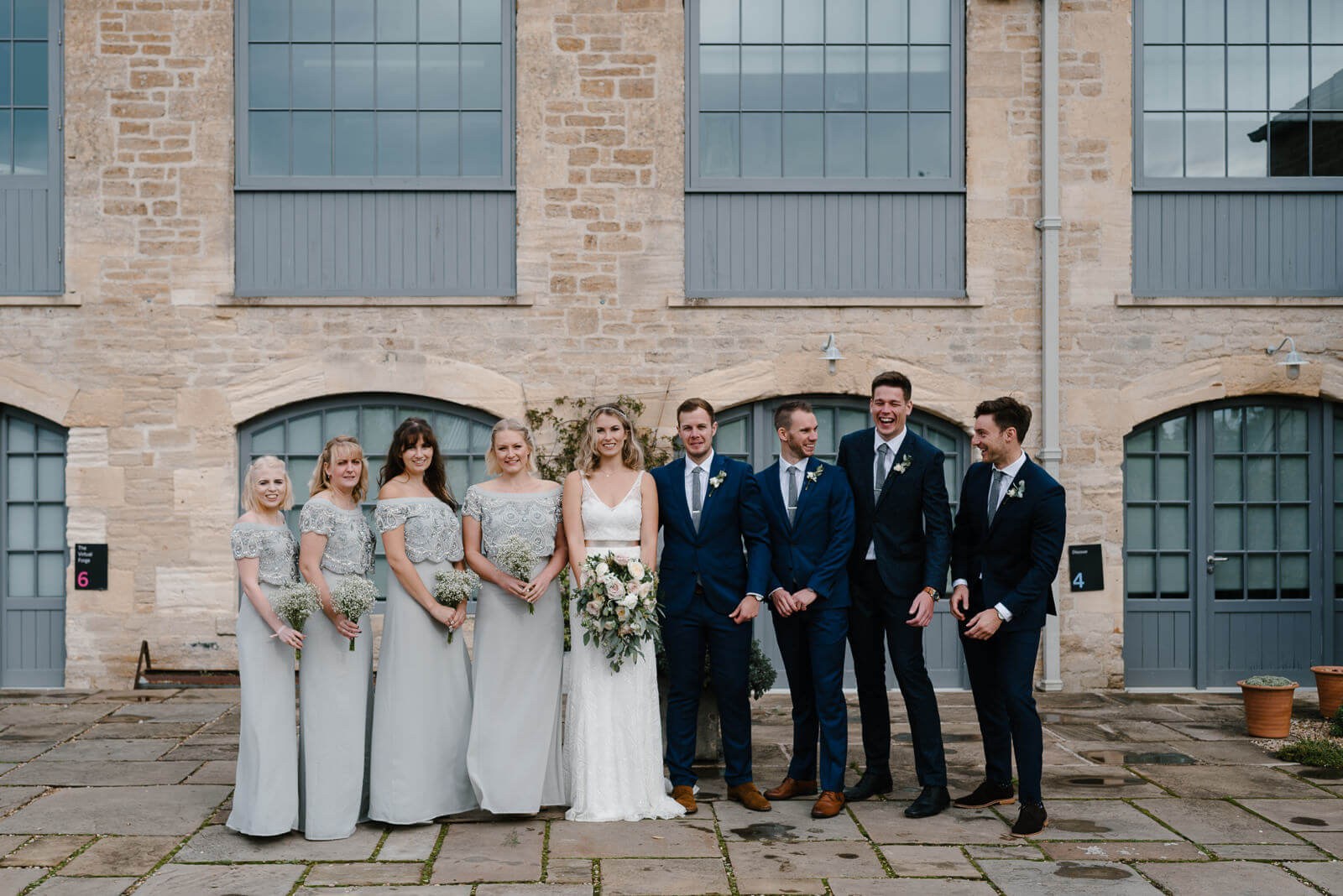 groomsmen laugh during wedding party portrait at Wiltshire venue, Glove Factory Studios